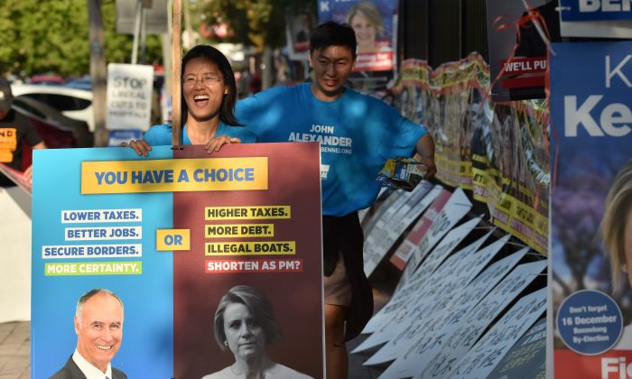 Supporters of Liberal MP John Alexander pack away banners outside a polling station at the close of voting in the suburban Sydney seat of Bennelong on Dec. 16, 2017. Electoral pressure by the Chinese Communist Party almost toppled the Australian government. (PETER PARKS/AFP/Getty Images)