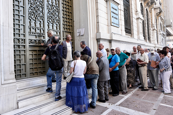 ATHENS, GREECE - JULY 20:  People wait to enter a bank branch as Greek banks reopened on Monday morning after three weeks of closure on July 20, 2015 in Athens, Greece. (Photo by Milos Bicanski/Getty Images)