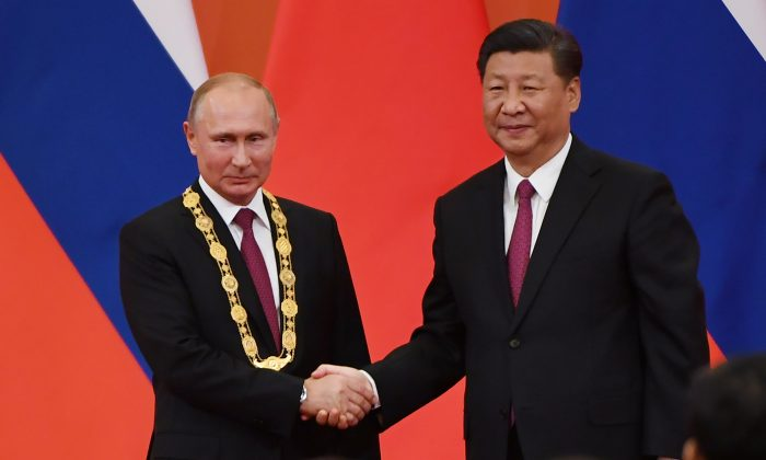 Chinese Communist Party leader Xi Jinping (R) congratulates Russian leader Vladimir Putin after presenting him with the Friendship Medal in the Great Hall of the People in Beijing on June 8, 2018. (GREG BAKER/AFP/Getty Images)