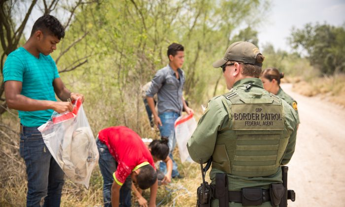 Border Patrol agents get illegal immigrants to put their belongings into plastic bags before transporting them to a processing facility, in Hidalgo County, Texas, on May 26, 2017. (Benjamin Chasteen/The Epoch Times)