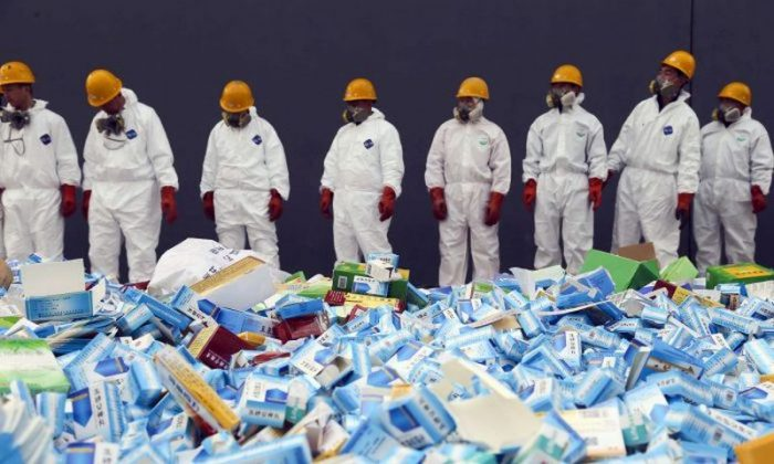 Chinese workers preparing to destroy fake medicines seized in Beijing, on March 14, 2013. The U.S. Food and Drug Administration announced on July 13, 2018 the recall of the heart medicine valsartan, made by Chinese firm Zhejiang Huahai, which was found to be contaminated by a carcinogen. (STR/AFP/Getty Images)