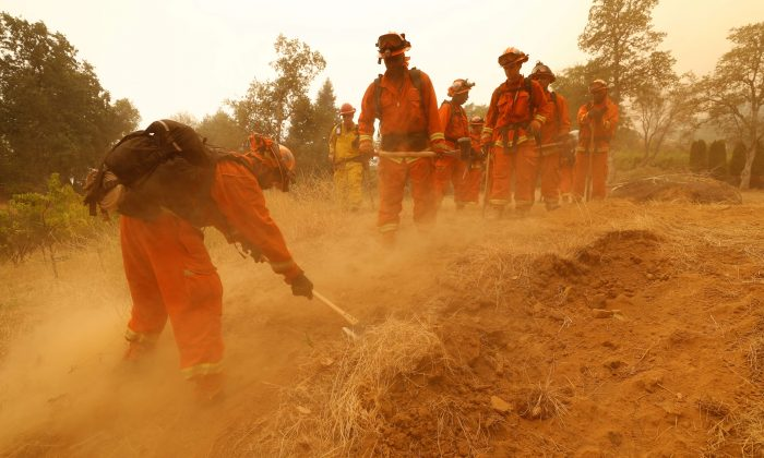 An inmate fire crew cuts fire lines in hot and smoky conditions while working to stop the spread of the Carr Fire, west of Redding. (Reuters/Fred Greaves)