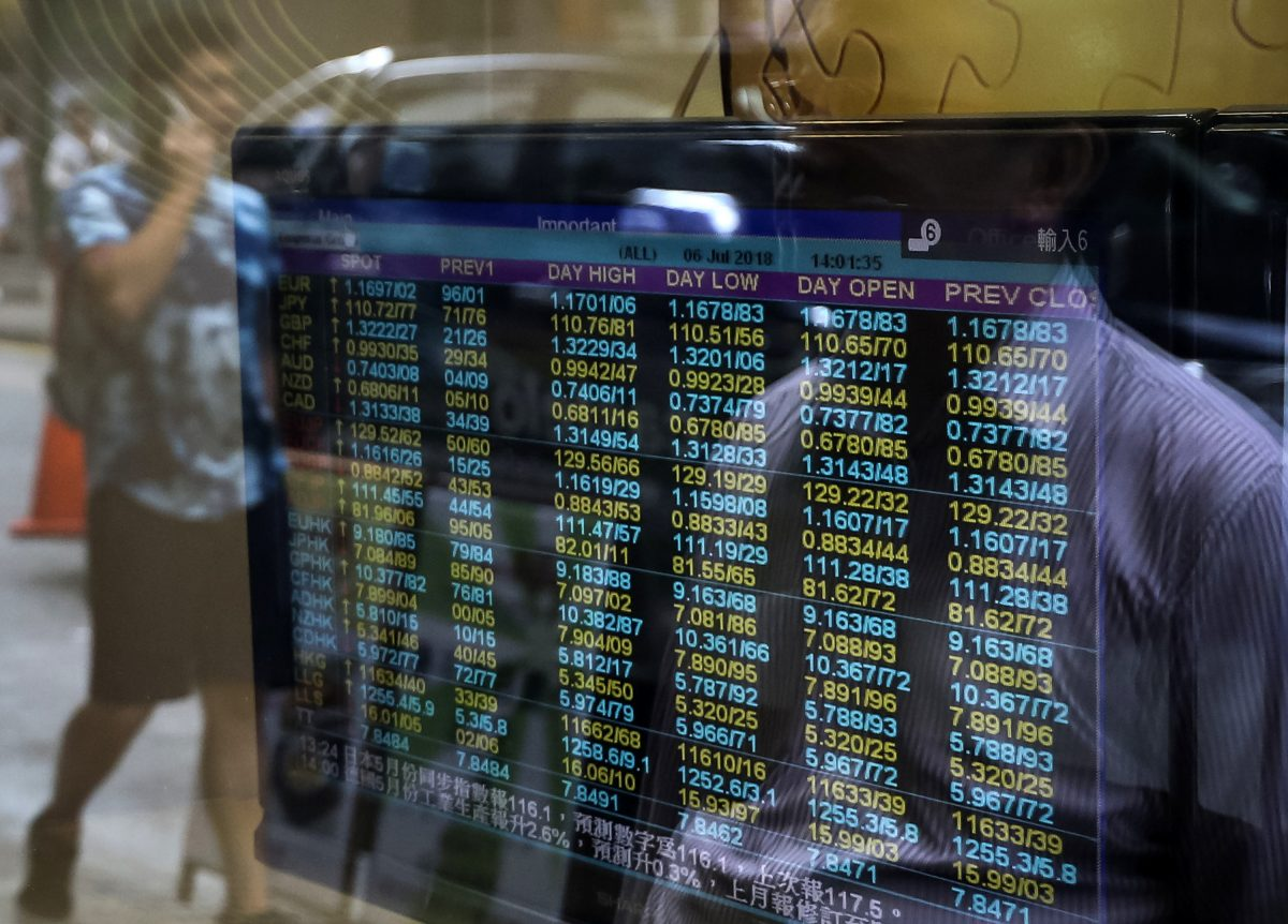 Pedestrians are reflected in the window of a brokerage with a screen showing currency exchange rates in Hong Kong on July 6, 2018. The yuan has dropped in value, following the imposition of U.S. tariffs on Chinese goods. (VIVEK PRAKASH/AFP/Getty Images)