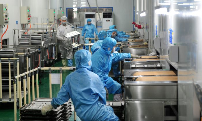 Employees work in a factory producing touchscreen glass, in Liuyang City, Hunan Province, on March 12, 2015.(STR/AFP/Getty Images)