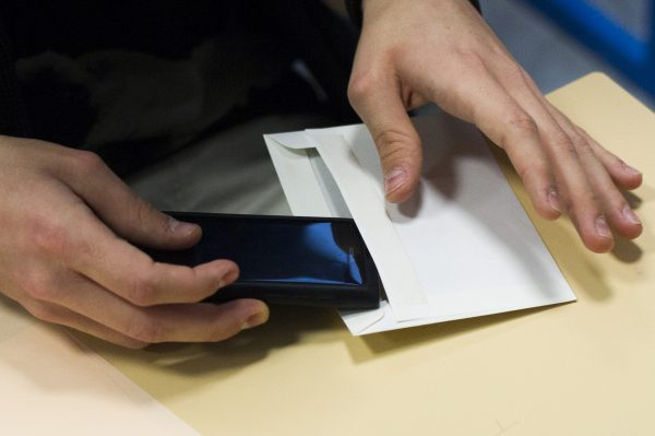 A French student puts his smartphone in an envelope to give it to supervisors before an exam at the Arago high school in Paris