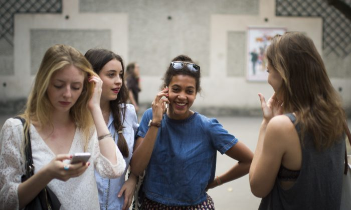 Students in France use their cellphones after viewing the results of the baccalaureat exam (high school graduation exam) on July 7, 2015, at the Georges Brassens secondary school in Paris. (Martin Bureau/AFP/Getty Images)