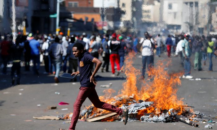 A man runs as supporters of the opposition Movement for Democratic Change party (MDC) of Nelson Chamisa burn barricades in Harare, Zimbabwe, August 1, 2018. (Reuters/Siphiwe Sibeko)