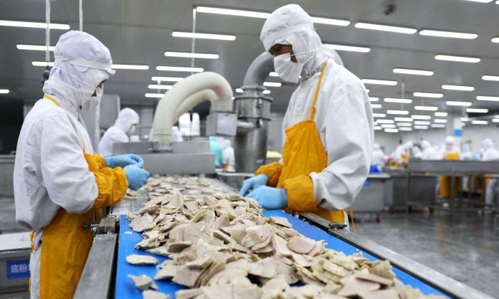 Workers process pork at a food factory in Rongcheng City, Shandong Province, on July 19, 2018. (AFP/Getty Images)