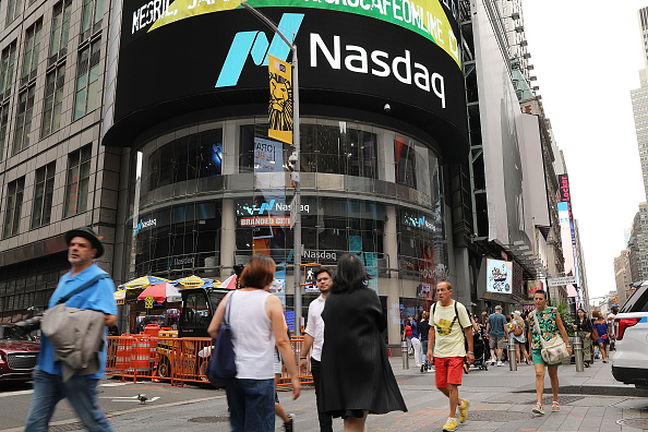 People walk by the Nasdaq MarketSite in Times Square on July 30, 2018 in New York City. (Spencer Platt/Getty Images)