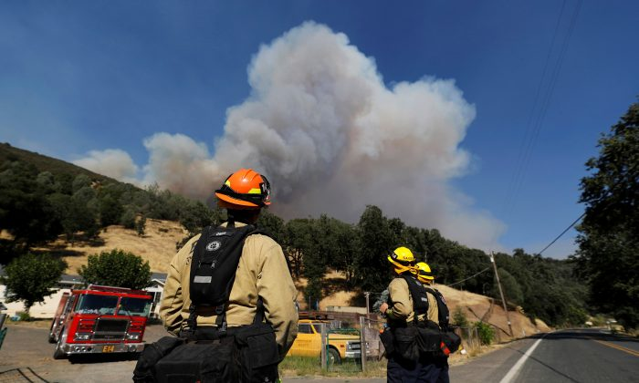 Firefighters on a structure protection team watch a plume of smoke grow from the Ranch Fire (Mendocino Complex) in the hills north of Upper Lake, California, U.S. August 1, 2018.  REUTERS/Fred Greaves