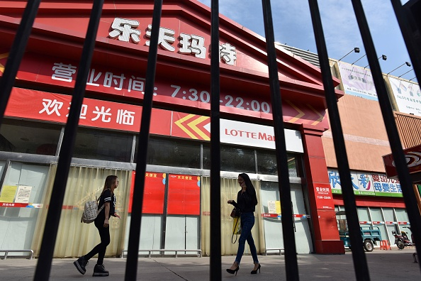 People walk past a closed Lotte Mart store in Beijing on Sept. 15, 2017. The South Korean conglomerate has recently completely withdrawn from the Chinese market. (Greg Baker/AFP/Getty Images)