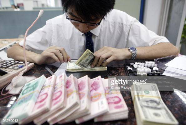 A clerk counts stacks of Chinese yuan and U.S. dollars at a bank in Shanghai on July 22, 2005. (China Photos/Getty Images)