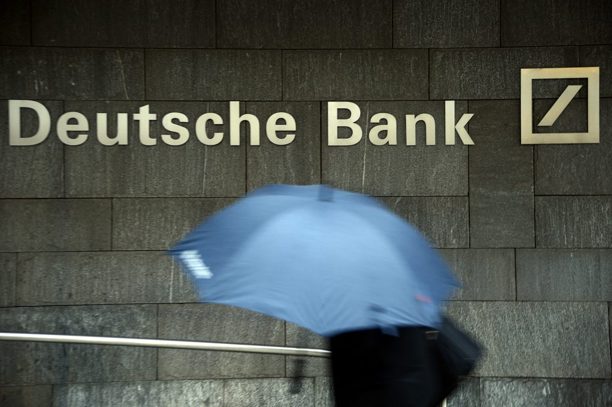 A woman with an umbrella passes a logo of Deutsche Bank in Frankfurt