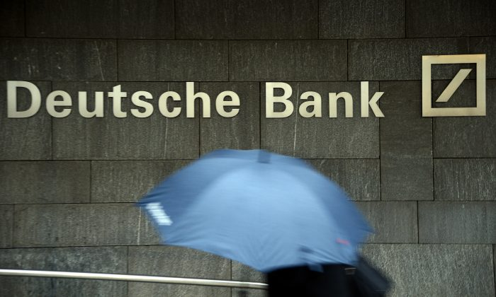 A woman with a umbrella passes a logo of Deutsche Bank on January 29, 2013 in Frankfurt am Main, Germany. (Thomas Lohnes/Getty Images)