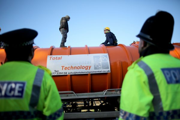 A policeman edges his way towards an anti-fracking protester standing on the top of a truck carrying chemicals to the Barton Moss gas fracking facility on Jan. 13, 2014 in Barton, England.