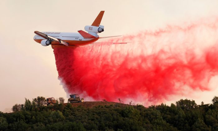 A DC-10 air tanker drops fire retardant along the crest of a hill to protect the two bulldozers below that were cutting fire lines at the River Fire near Lakeport, California, U.S. on August 2, 2018.  (REUTERS/Fred Greaves)