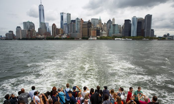 With Lower Manhattan in the background, visitors and tourists ride a ferry toward Liberty Island and the Statue of Liberty in New York City, August 8, 2017. (Drew Angerer/Getty Images)