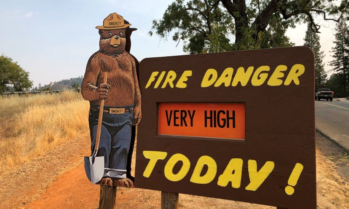 A sign by the side of the road warns of the threat of wildfires which have been fueled by continued hot weather outside the town of Colfax, California, U.S., Aug. 4, 2018. (Reuters/Jim Christie)
