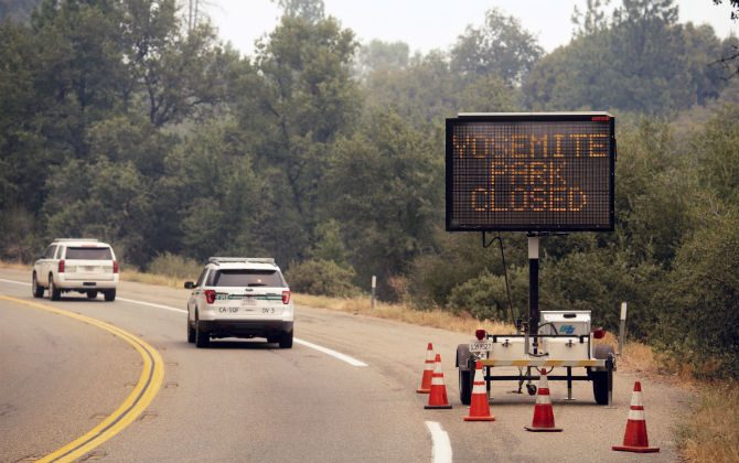 In this July 25, 2018 file photo, a sign on Highway 41 announces the closure of Yosemite National Park near Oakhurst, Calif. Yosemite National Park could reopen its scenic valley and other areas Monday, Aug. 6, 2018, if conditions improve after a 12-day closure due to nearby wildfires. (AP Photo/Noah Berger, File)