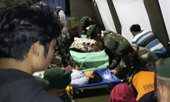 Indonesian soldiers tend to a woman injured in the earthquake at a makeshift hospital in Lombok, Indonesia, Aug. 5, 2018. (AP Photo)