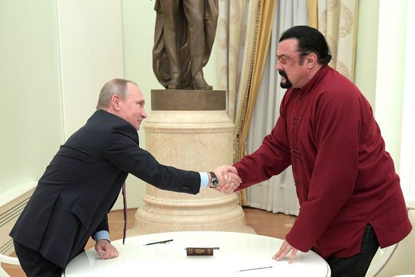 Russian President Vladimir Putin (L) shakes hands with U.S. action hero actor Steven Seagal after presenting a Russian passport to him during a meeting at the Kremlin in Moscow on November 25, 2016. (ALEXEY DRUZHININ/AFP/Getty Images)