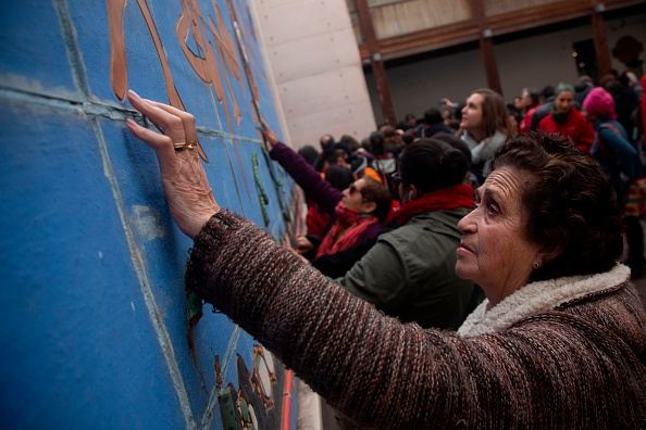 A blind woman touches a mural on July 10 in Santiago, Chile. (CLAUDIO REYES/AFP/Getty Images)