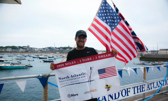 In this Saturday, Aug. 4, 2018 photo provided by Bryce Carlson Adventures, Bryce Carlson poses for a photo after completing his solo unsupported row across the Atlantic, at St Mary's Harbour, Isle of Scilly, England. (Bryce Carlson Adventures via AP)