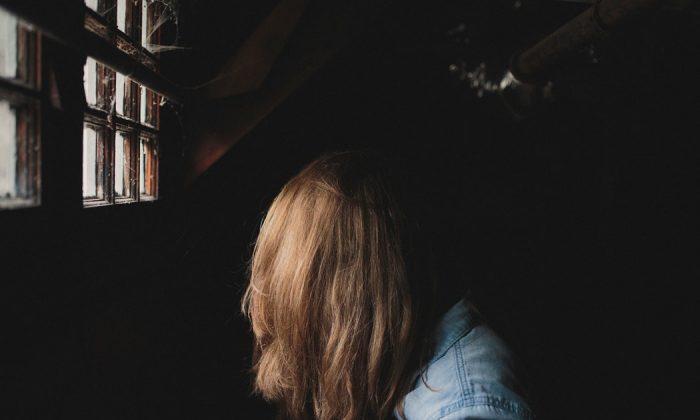 A female sitting sideways in a denim jacket. (Unsplash)