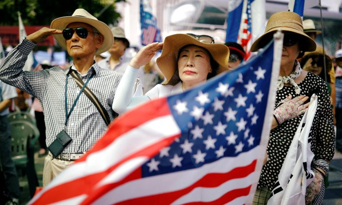 Members of a conservative civic group salute to a U.S. national flag during an anti-North Korea and pro-U.S. protest in Seoul, South Korea, Aug. 4, 2018. (Reuters/Kim Hong-Ji)