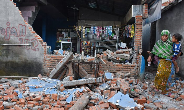 A woman walks past debris from a collapsed wall following a strong earthquake in Lendang Bajur Hamlet, Lombok island, indonesia on Aug. 6, 2018. (Antara Foto/Ahmad Subaidi/ via REUTERS)