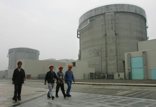 Workers at the Qinshan nuclear power plant walk past containment structures hosing nuclear reactors, in Jiaxing City, Zhejiang Province, on June 10, 2005. (Frederic J. Brown/AFP/Getty Images)