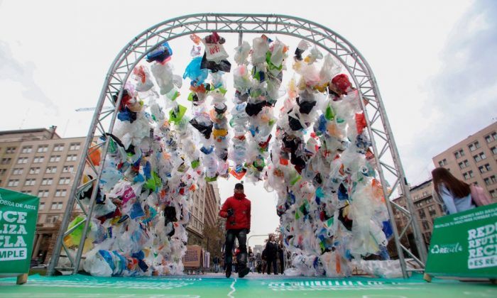 People walk through a tunnel made out of plastic bags in front of La Moneda presidential palace in Santiago, during the World Environment Day on June 5, 2018. - The UN urged to take steps against the use of plastic bags, as part of a global challenge to reduce the increasing pollution of the oceans. (Claudio Reyes/AFP/Getty Images)