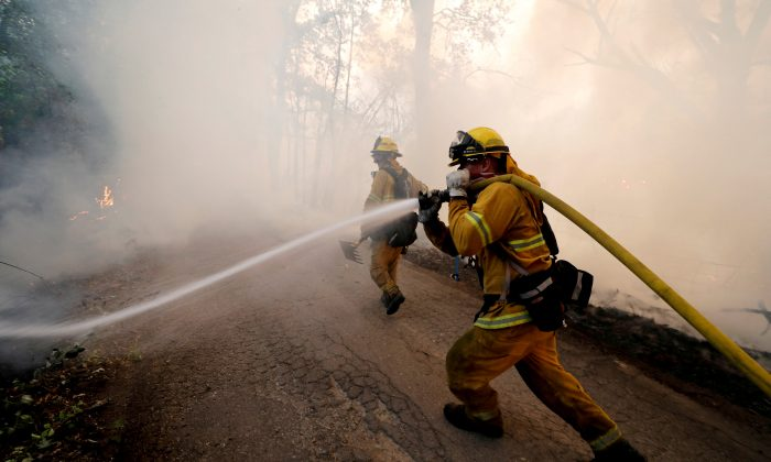 A firefighter knocks down hotspots to slow the spread of the Mendocino Complex fire in Lakeport, California on July 31, 2018. (Fred Greaves/Reuters)