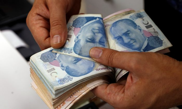 A money changer counts Turkish lira banknotes at a currency exchange office in Istanbul, on Aug. 2, 2018. (Reuters/Murad Sezer)