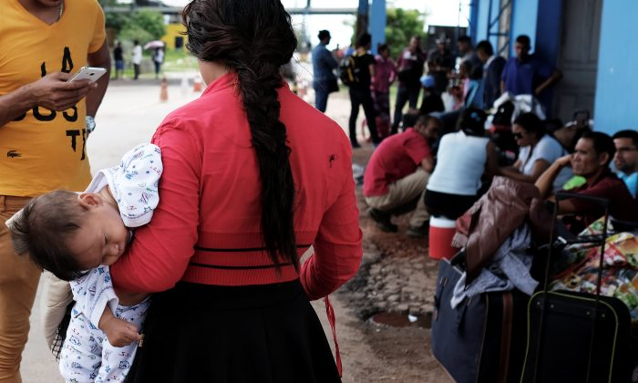 Venezuelans are pictured with their luggage before showing their passports or identity cards at the Pacaraima border control, Roraima state, Brazil Nov. 16, 2017. (Reuters/Nacho Doce)