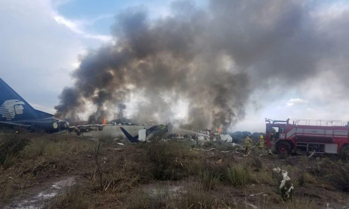 Firefighters douse a fire as smoke billows above the site where an Aeromexico-operated Embraer passenger jet crashed in Mexico's northern state of Durango, July 31, 2018, in this picture obtained from social media. (Proteccion Civil Durango/via Reuters)