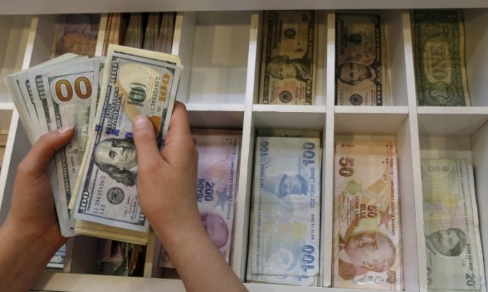 A money changer counts U.S. dollar bills, with Turkish lira banknotes in the background, at an currency exchange office in central Istanbul, Turkey, on Aug. 21, 2015. (Reuters/Murad Sezer)