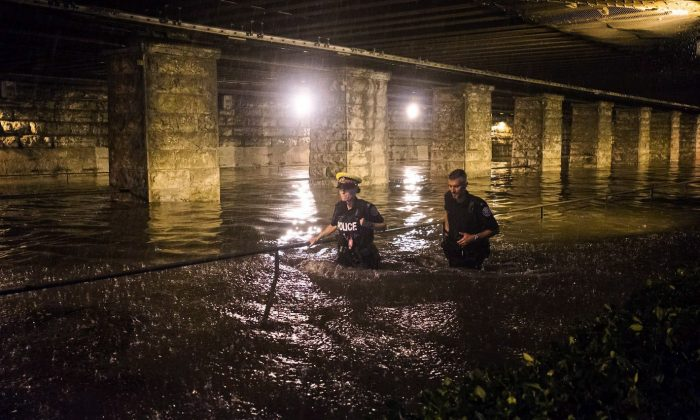 Police officers wade through water flooding an underpass on King St. W. during heavy rain in Toronto on Tuesday, August 7, 2018. (The Canadian Press/Shlomi Amiga)