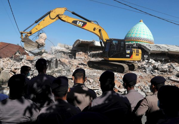 Policemen stand as heavy equipment move debris for try to find people trapped inside a mosque after an earthquake hit on Sunday in Pemenang, Lombok Island, Indonesia, Aug. 8, 2018.