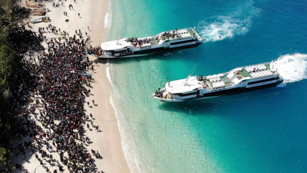 Boats arrive at shore to evacuate people on the island of Gili Trawangan, Lombok, Indonesia, Aug. 6, 2018, in this still image taken from a drone video obtained from social media.