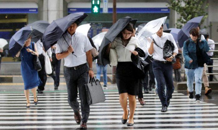 Passersby using umbrellas struggle against a heavy rain and wind as Typhoon Shanshan approaches Japan's mainland in Tokyo, Japan Aug. 8, 2018. (Reuters/Toru Hanai)