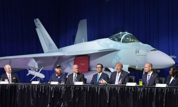 President Donald Trump (3R) speaks as Boeing CEO Dennis Muilenburg (2R) and US Secretary of the Treasury Steven Mnuchin  (C) look on in front of an FA-18 Super Hornet during a tour of the Boeing Company in St. Louis, Missouri on March 14, 2018. (Photo credit should read MANDEL NGAN/AFP/Getty Images)