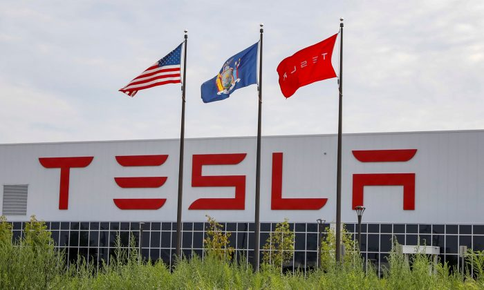 Flags fly over the Tesla Inc. Gigafactory 2, which is also known as RiverBend, a joint venture with Panasonic to produce solar panels and roof tiles in Buffalo, New York, U.S., August 2, 2018. (Reuters/Brendan McDermid)