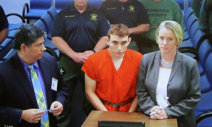 Nikolas Cruz (C) appears via video monitor with Melisa McNeill (R), his public defender, at a bond hearing after being charged with 17 counts of premeditated murder, in Fort Lauderdale, Fla., Feb. 15, 2018. (Susan Stocker/Pool/Reuters)