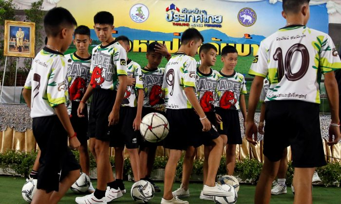 Twelve 'Wild Boars' soccer players and their coach play soccer as they arrive for their news conference in Chiang Rai, Thailand July 18, 2018. (Reuters/Soe Zeya Tun)