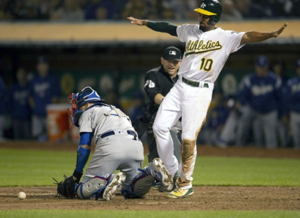 Oakland Athletics shortstop Marcus Semien signals safe after sliding home ahead of the relay to Los Angeles Dodgers catcher Yasmani Grandal (left) during the eighth inning.
