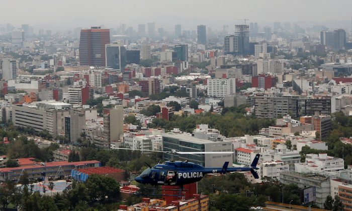 "Police officers, members of a team known as ""Condores"", stand by the door of the helicopter during a patrol of the city, part of a new strategy to combat the crime in Mexico City, Mexico Aug. 3, 2018. (REUTERS/Carlos Jasso)"