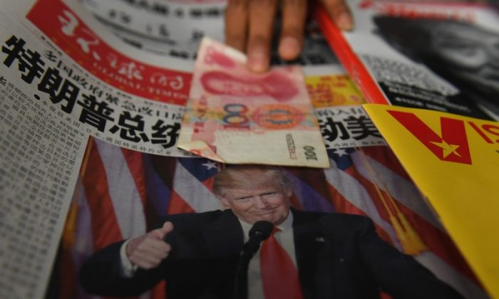 A vendor picks up a 100 yuan note above a newspaper featuring a photo of President-elect Donald Trump, at a news stand in Beijing on Nov. 10, 2016. (Greg Baker/AFP/Getty Images)