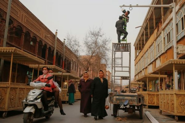 Men install a CCTV camera in a shopping street in the old town of Kashgar, Xinjiang Uighur Autonomous Region, China.