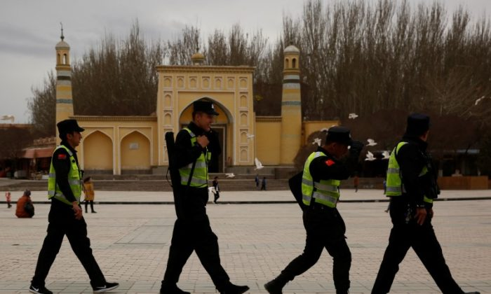 Police patrol walk in front of the Id Kah Mosque in the old city of Kashgar, Xinjiang Uighur Autonomous Region, China. (Reuters/Thomas Peter)